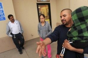 PHOTO BY ROB VARELA, VENTURA COUNTY STAR ROB VARELA/THE STAR Andres Castro holds his son Andres Jr. in Oxnard's La Colonia neighborhood on Tuesday. Castro and his wife, Esperanza Gonzalez (center), live in an apartment near the corner where Oxnard police officers shot and killed a man they mistook for a suspect last year. Rigoberto Gonzalez (left) is part owner of the building.