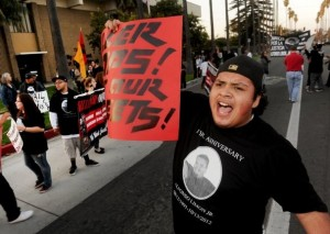 ROB VARELA/THE STAR Leonardo Suarez leads a chant outside the Oxnard Police Department as marchers marking the year anniversary of Alfonso Limon Jr.'s shooting by Oxnard police, make their way through the streets of Oxnard on Sunday.