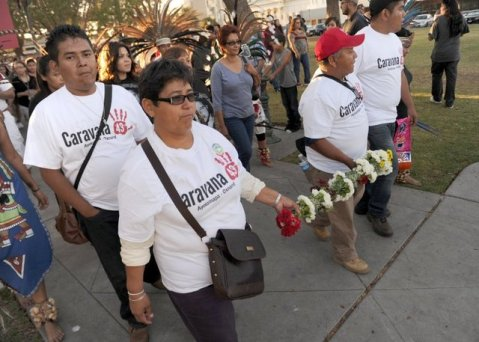 ROB VARELA/THE STAR Blanca Luz Nava Velez (second from left) and Estanislao Mendoza Chocolate, part of the Caravana 43, hold a cane covered with 43 white flowers that was made and presented to them by local dancers as they lead a march Thursday in Oxnard. Velez's son Jorge and Chocolate's son Miguel are among 43 students missing in Mexico.