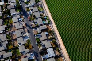 An aerial view of homes alongside strawberry fields in Oxnard, California, U.S. on Wednesday May 21, 2014.